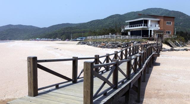 해변가 모래사장 위에 나무다리가 보이며 멀리 드라마 촬영지 건물이 보이는 풍경 사진 이미지입니다.
