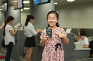 도심공항터미널 견학 사진 이미지입니다. 초등학생 여자아이가 여권을 들고 있는 모습입니다.