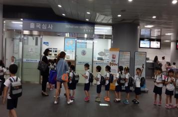 법무부 출입국 관리사무소 견학 사진 이미지입니다. 출국심사를 받기 위해 유치원생 아이들이 일렬로 줄을 서서 기다리고 있는 모습입니다.