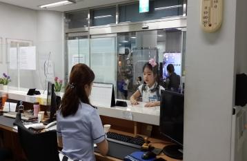 샘플 여권을 출국심사자에 내밀고 심사를 받고 있는 어린 여자아이의 모습입니다.