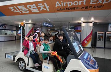 인천국제공항역 전동카트에 5명의 어린 아이들이 함께 타고 시승을 하고 있는 모습입니다.