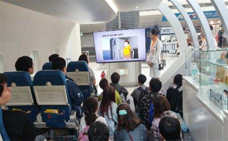 인천국제공항역 게이트에 바로 앞에 항공안전라운지 체험부스가 있으며, 여러명의 어린이들이 안내 승무원의 설명을 듣고 있는 모습입니다.