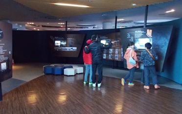 홍보관 학습자료 실내에서 대형 디스플레이 앞에 관람객 4명이 서있는 모습입니다.