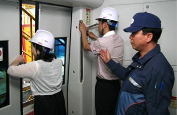 안전모를 착용한 실습명 두명에 공항철도 열차 출입문를 강제로 열고 있는 모습입니다.