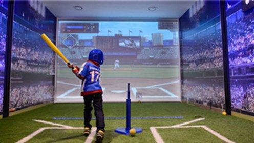 밸런스 파크내 야구 체험부스에서 가상의 시뮬레이션으로 야구모를 쓰고 야구공을 치는 어린아이의 모습입니다.